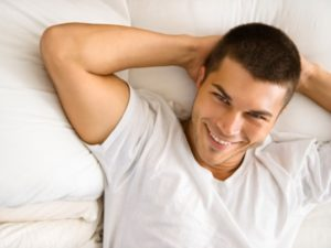 smiling man leaning back against pillow on the bed