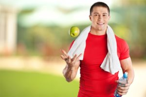 man tossing apple and holding water bottle during workout