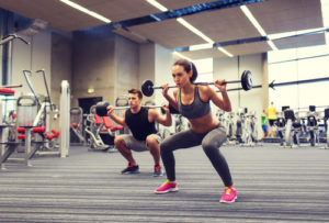fit couple doing barbell squats in gym