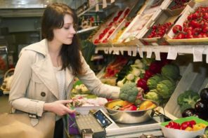 woman weighing vegetables in grocery
