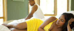 disappointed woman laying in bed with man far on the other side
