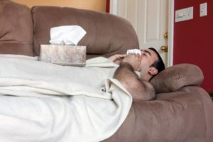 man with colds sneezing and laying on couch