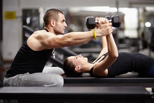 trainer assisting woman with dumbbell chest press