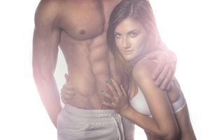 woman hugging man with six pack abs