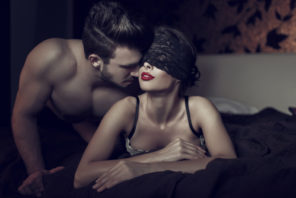 man kissing blindfolded woman getting intimate in bed