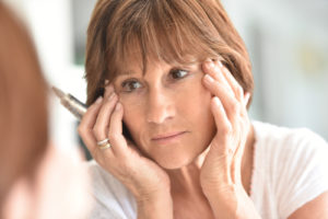 middle aged woman looking at wrinkles on face