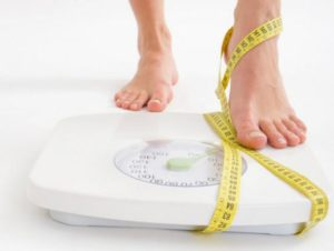 stepping on weighing scale with tape measure wrapped around ankle