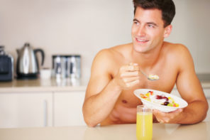 shirtless man with a bowl of fruit salad in the kitchen