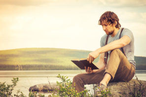 man relaxing and reading a book outdoors