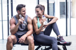 couple taking a break from gym workout drinking water