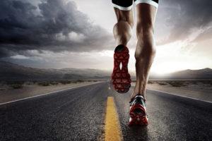 legs of man running on road