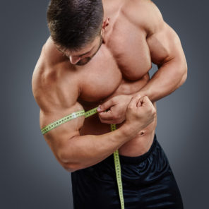 fit muscular guy measuring bicep circumference