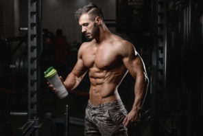 fit guy holding water bottle with protein drink