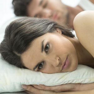 disappointed woman in bed with man sleeping beside her