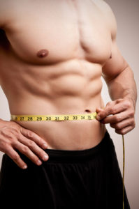 fit guy with abs measuring waist circumference
