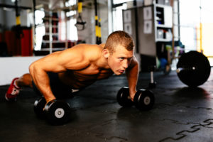 fit guy doing barbell push ups