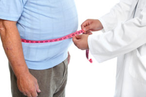 doctor measuring overweight patient's waist circumference