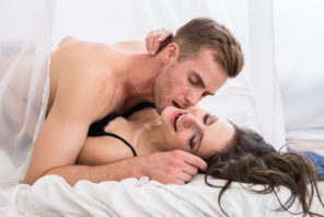 couple getting intimate in bed kissing