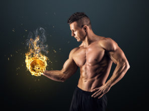 fit muscular guy holding dumbbell on fire
