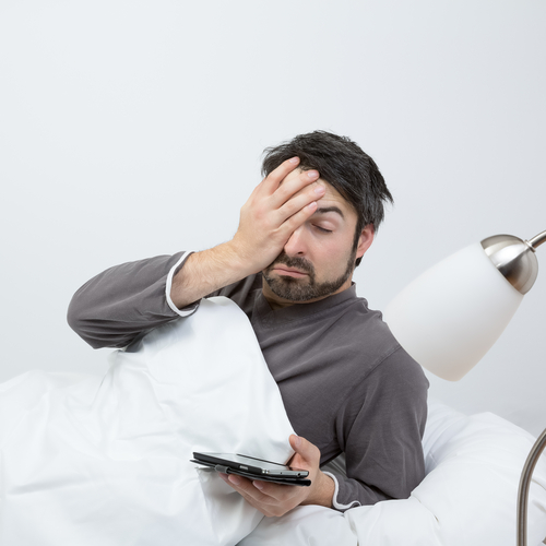 man who just woke up checking his phone