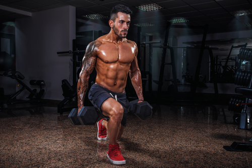fit muscular man doing lunges with dumbbells
