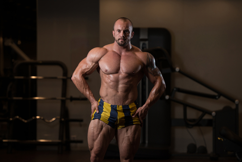 muscle guy standing in gym in boxers