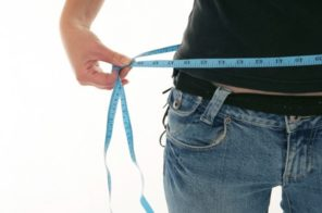 man measuring waist to show weight loss