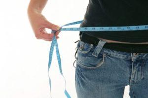 man measuring waist to show weight loss