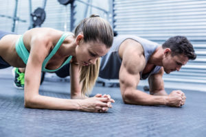 fit couple doing planks together in the gym