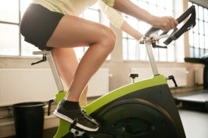 woman exercising on stationary bike