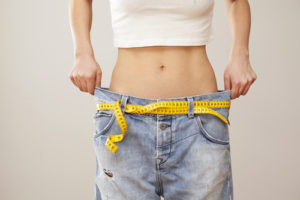 woman wearing oversize jeans showing weight loss