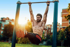 fit guy doing pull ups in park