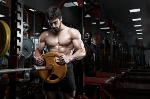 fit muscular guy setting up weights in gym