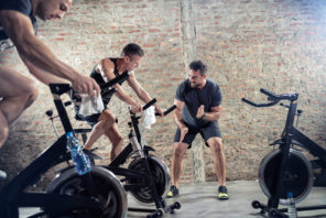 trainer motivating group cycling on stationary bikes