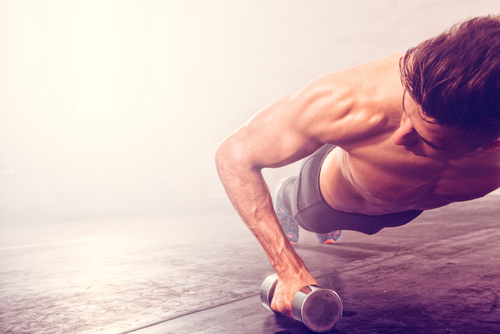 fit guy doing push ups with dumbbell