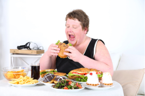 overweight man eating excessive amount of junk food