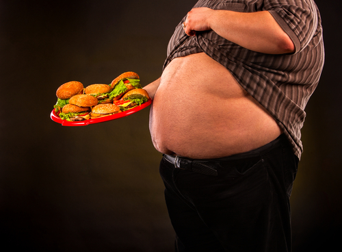 obese man exposes belly holding plate full of burgers