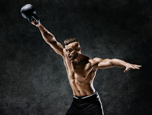 fit man doing one hand kettle bell swing