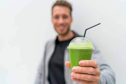 man holding out green smoothie