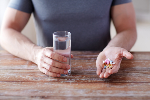 multivitamon and Progentra supplement pills in man's hand