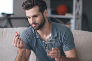 man looking at vitamin capsule in hand and learning about Progentra