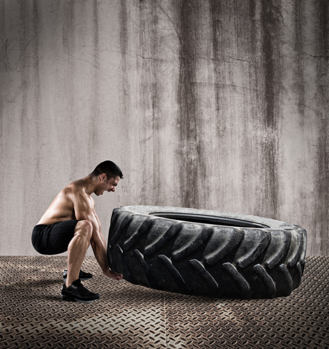 man lifting oversized tire