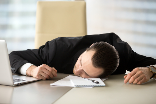 exhausted man passed out on office desk