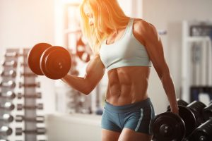 muscular woman with abs lifting heavy weight