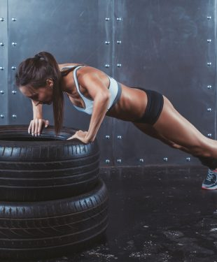 fit woman doing push up on tires