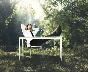 man relaxing on chair, feet up in forest