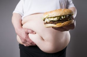 obese man holding belly fat and a burger