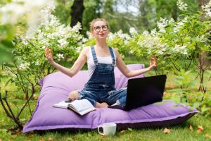 zen woman in garden with book and laptop