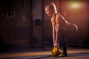 fit woman doing squats with kettle bell in gym