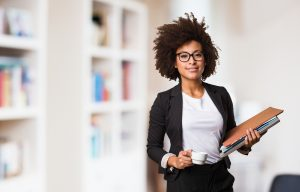 working woman in office holding coffee and files